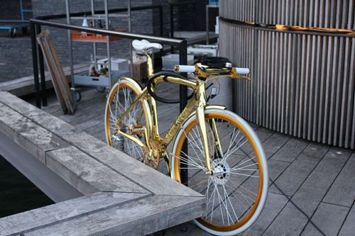 A gold frame Avenue Cykler using a cable lock.  Most bikes there just use wheels locks. That is one hot bike.