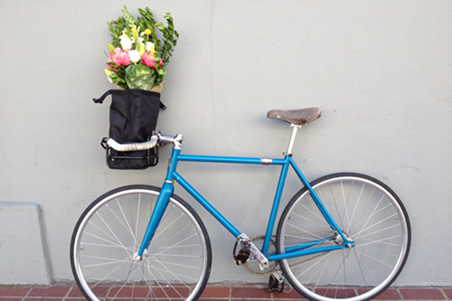 A blue fixie about to deliver flowers to a lucky woman