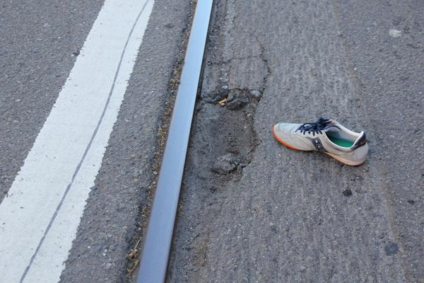 A close-up a cracked pavement that developed into a pothole.