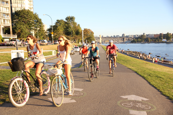 Canadians biking near the English Bay.
