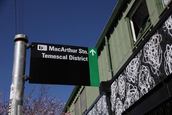 Street sign indicating green sharrow bike path leading to MacArthur BART Station