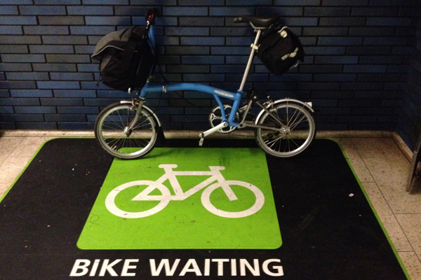 My Brompton with a full Brompton C Bag and a full Carradice Nelson long flap saddle bag at an Oakland BART station.